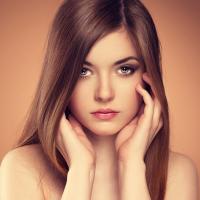 Hair, skin care. Beautiful sensual woman touching her face