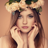Spring girl. Young elegant woman with roses bouquet in hair